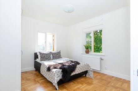 Sovrum med vacker ekparkett på golvet och fönster i två väderstreck.