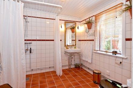 Stort och praktiskt badrum med wc, tvättställ, dusch och fönster
