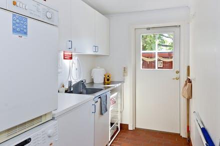 Groventré/tvättstuga med dörr till den egna trädgården