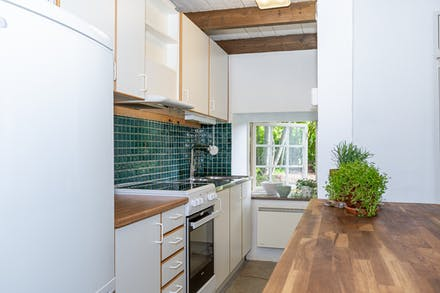 Kök med vit inredning och fönster mot norr.