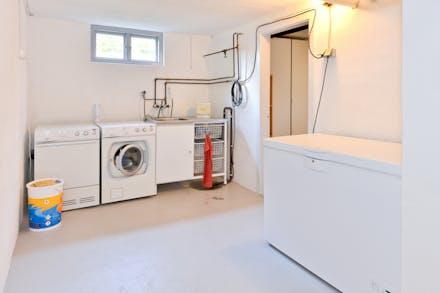 Tvättstuga med tvättmaskin, torktumlare och frysbox