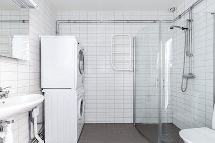 Stort helkaklat badrum med egen tvättmaskin och tumlare.