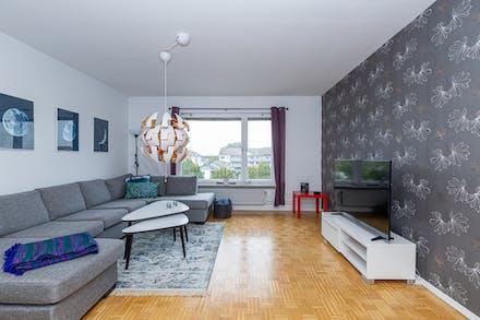 Stort vardagsrum med parkettgolv och ett härligt ljusinsläpp