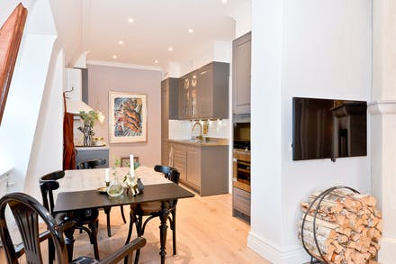Trivsam interiör som har en öppen planlösning mellan kök, matrum och vardagsrum