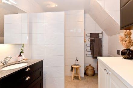 Badrum med tvättmaskin och torktumlare dolda i vit skåpinredning