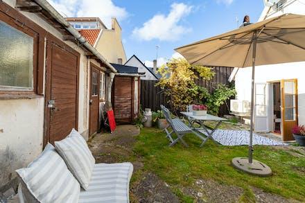 Trädgård med uthuslänga och plats för utemöbler