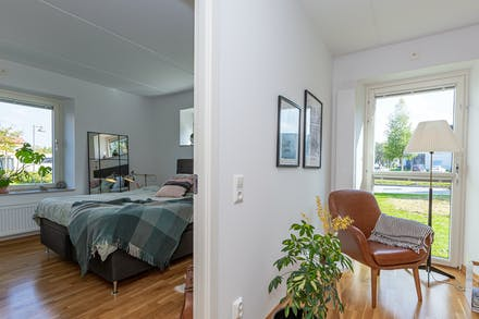 Utanför sovrum 2 ligger vardagsrummet som har en helglasad gavelutgång till föreningens grönyta