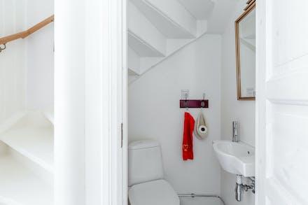 Vid entrén och invid ena trappan till övre plan finns separat toalett med wc och tvättställ