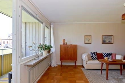 Vardagsrum med ekparkett och utgång till balkong