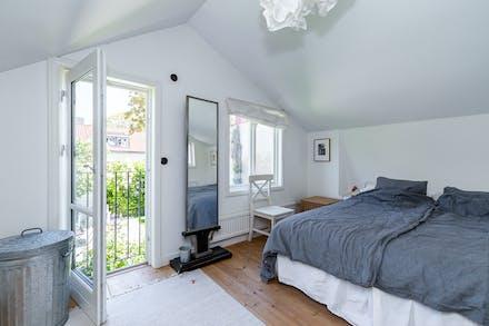 Sovrum 1 med trägolv och fransk balkong mot den egna trädgården