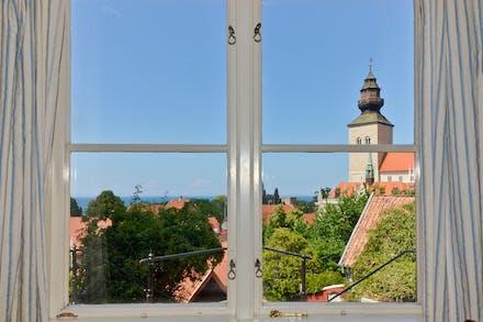 Utsikt med grönska, hustak, Visby domkyrka och havet
