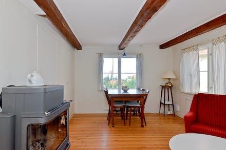 Vardagsrummet har takbjälkar, trägolv och fönster i två väderstreck