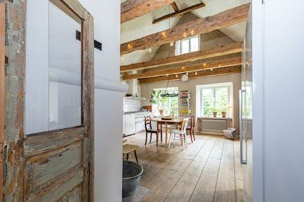 Äldre dörrar leder in i köket med vackra breda golvtiljor och frilagda takbjälkar