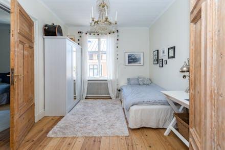 Sovrum 2 med trägolv och fönster mot Tranhusgatan (finns även anslutande dörr till sovrum 3)
