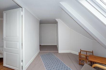 Övre möblerbar hall med målat trägolv och dörröppning till sovrum 3
