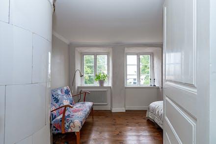 Sovrum 3 med trägolv och kakelugn (ej i funktion) samt fönster mot den egna gården