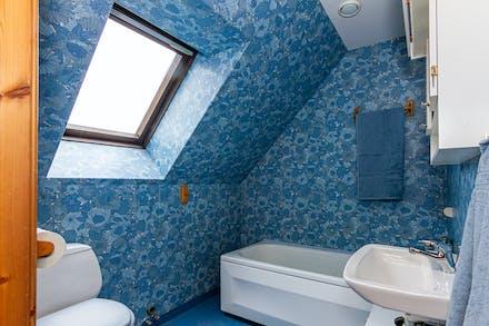 Badrum på övre plan med badkar och takfönster.