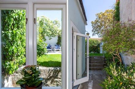 Vy mot trädgård / helglasad dörr från kök
