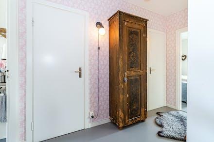 Hall/entré med gråmålat parkettgolv samt dörr till badrum
