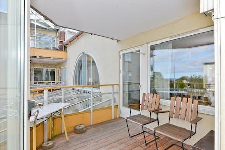 Stor balkong under tak med plats för bord och stolar