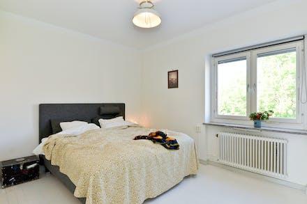 Sovrum med målade trägolv och fönster mot Lännaplan