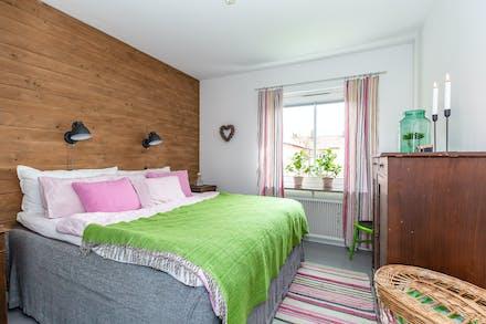 Sovrum med gråmålat parkettgolv och fönster mot föreningens innergård