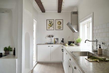 Stilrent kök med kalkstensbänkskiva och fönster mot havet