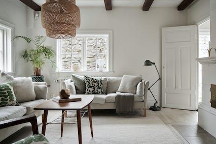 Vardagsrum med vitkalkade golv och fungerande kakelugn